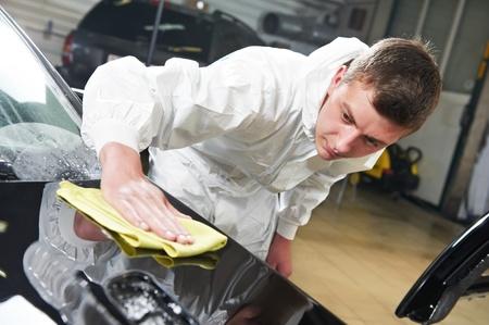 car maintenance: mechanic repairing and polishing car headlight Stock Photo