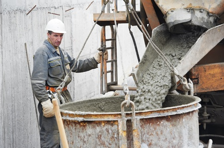 Builder worker pouring concrete into barrel photo