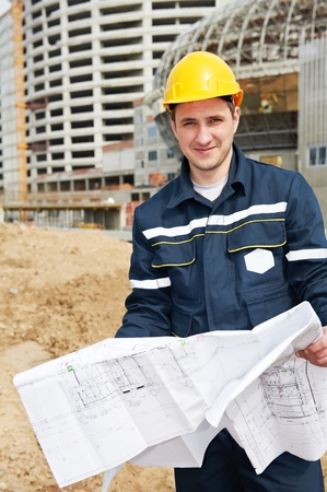 foreman at construction site with working drawings photo