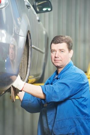 mechanic installing car wheel at service station photo