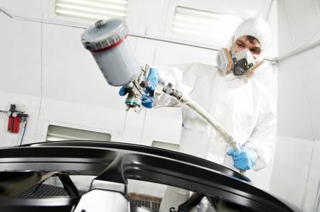 auto service: auto mechanic painting car bumper