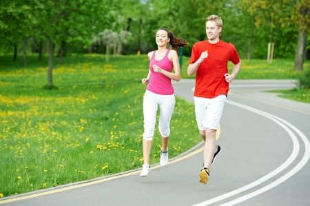 Young man and woman jogging outdoors photo