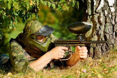 gun fire: paintball player aiming with marker  Stock Photo