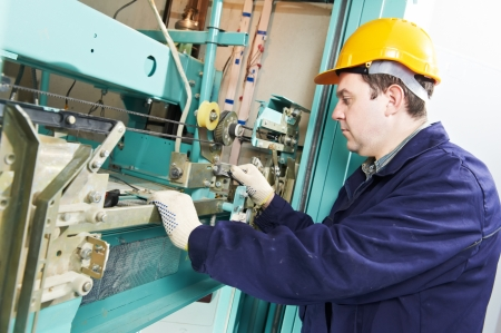 service lift: machinist with spanner adjusting lift mechanism