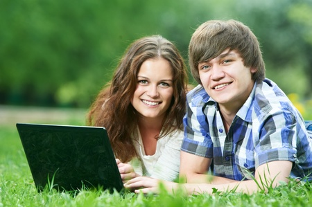 two smiling young students outdoors with computer photo