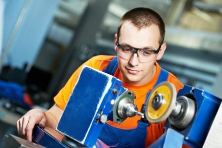 sharpening: industrial worker at sharpening machine tool