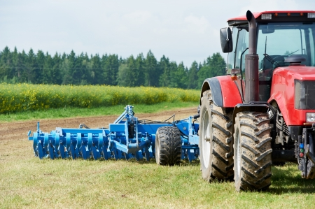 fatten: Ploughing tractor at field cultivation work