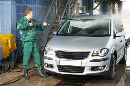 washing car: worker cleaning car with pressured water