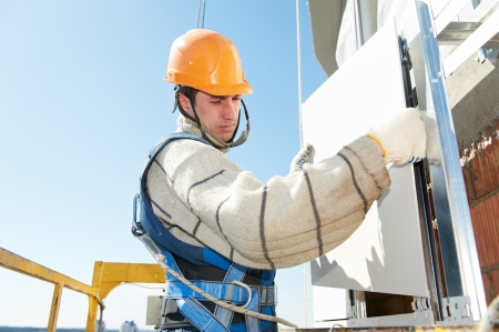 tile cladding: builder at aerated facade tile installation