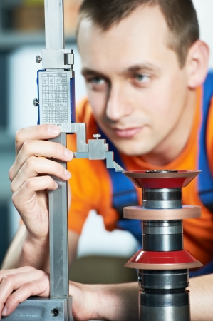 machinist: worker measuring cutting tool Stock Photo