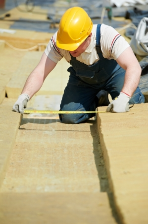 roofing membrane: roofer worker measuring insulation material