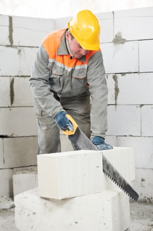 mason worker bricklayer with hand saw photo
