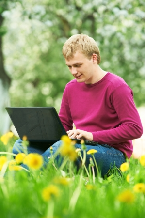 young student outdoors with computer photo