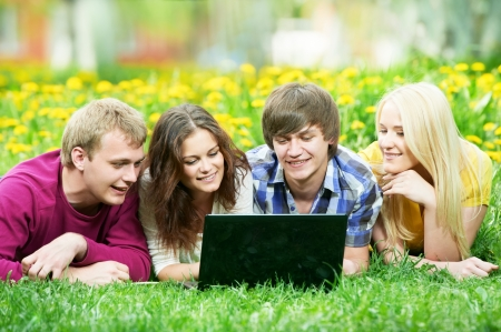 young students group with computer outdoors photo