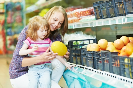woman and little girl shopping fruits photo