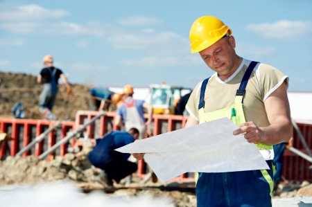 taskmaster: Engineer builders at construction site with draft Stock Photo