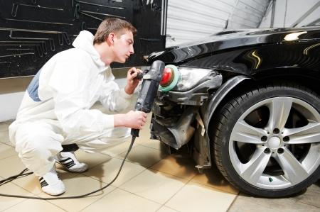 headlights: mechanic repairing and polishing car headlight Stock Photo