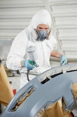 auto mechanic painting car bumper photo