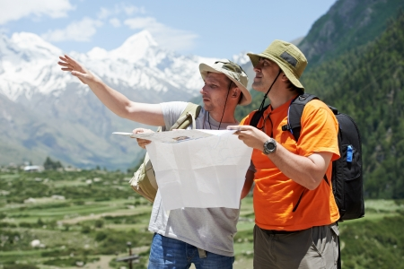 travel guide: Tourist travellers with map in mountains