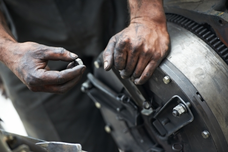 auto mechanic hands at car repair work photo