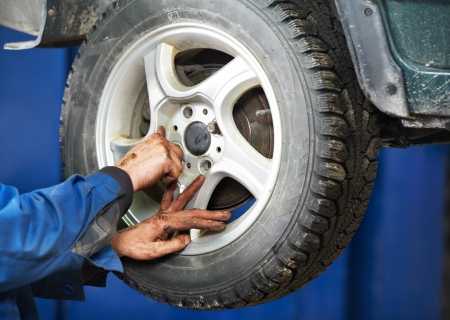 mechanic installing car wheel at service station photo