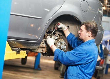 disassembly: auto mechanic at car suspension repair work