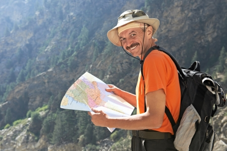 travel guide: Tourist hiker with map in mountains