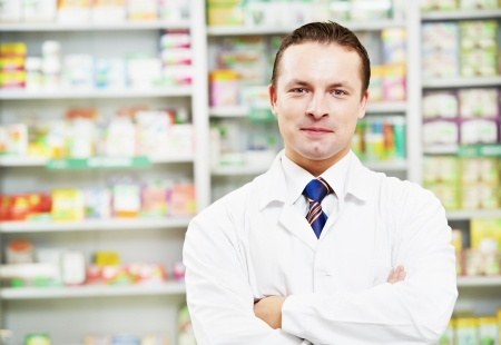 Confident pharmacy chemist man in drugstore photo