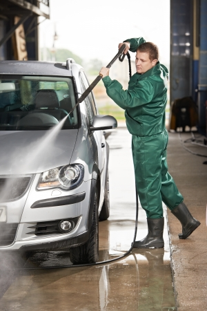 car service station: worker cleaning car with pressured water