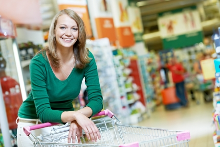woman shopping cart: One shopping woman with cart at supermarket Stock Photo