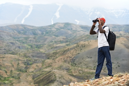 Tourist hiker with binoculars in mountains photo