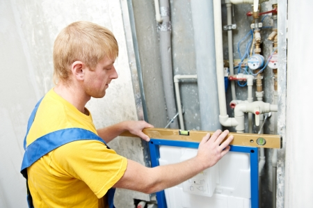 Young plumber worker checking installation system at toilet photo