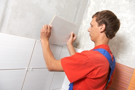 tiler installing wall tile at home repair renovation work photo