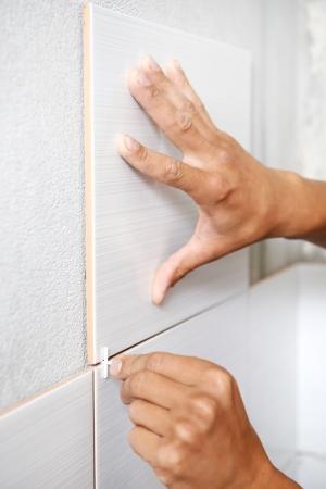 tegelwerk: Close-up van tegelzetter handen vaststelling wandtegel met afstandhouders thuis Reparatie renovatie Stockfoto