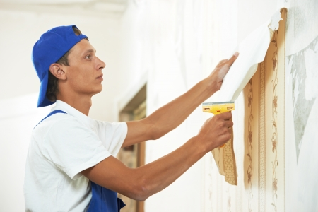 painter and decorator: One painter worker peeling off wallpaper during interior home repair renovation work Stock Photo