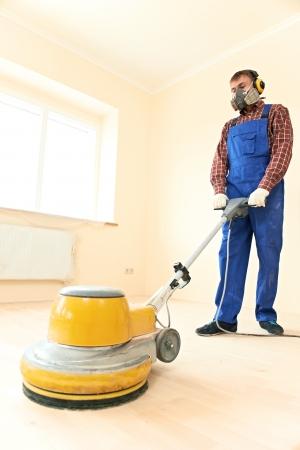 Worker carpenter doing parquet Wood Floor maintenance work by grinding machine Stock Photo - 21807508