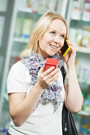 Young woman customer consulting by mobile phone at pharmacy medical drugstore