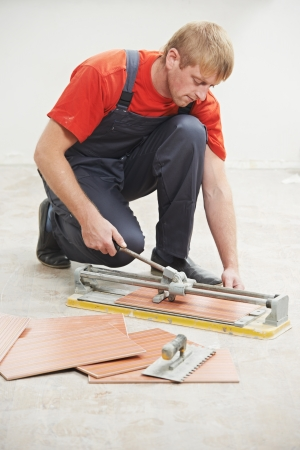tile cutter: One tiler using tile cutter at home repair renovation work Stock Photo