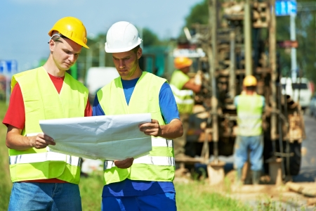 roadwork: Two engineer site managers builders with blueprint plan at geology roadwork construction site Stock Photo