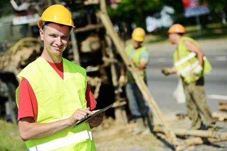 Una feliz y sonriente ingeniero constructor de sitios gerente con tablet PC en la geología del sitio de construcción obras viales Foto de archivo