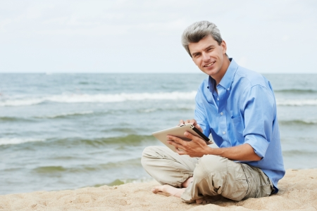 One young smiling man with tablet pc sittingon seashore photo