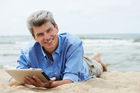 One young smiling man with tablet pc lying on seashore photo