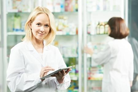 Happy Pharmacy chemist woman in drugstore photo