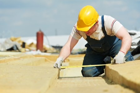 site preparation: roofer worker measuring insulation material