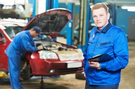 happy mechanic technician at service station photo