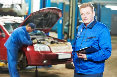 automobile workshop: happy mechanic technician at service station