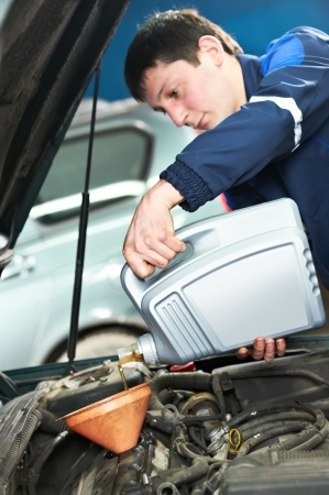 replacing: auto mechanic technician replacing and pouring motor oil into automobile engine at maintenance repair service station