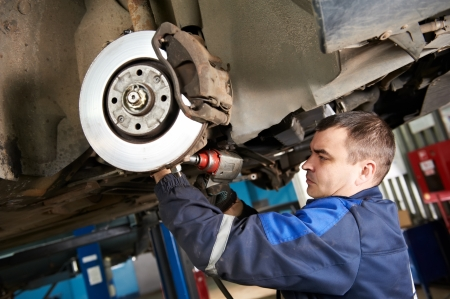 automobile workshop: car mechanic examining car suspension of lifted automobile at repair service station