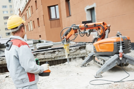 foremaster: builder worker in safety protective equipment operating construction demolition machine robot Stock Photo