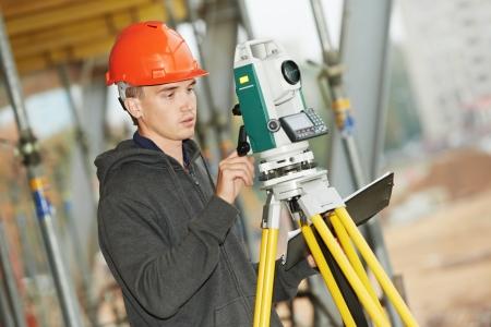 teodolito: Un trabajador agrimensor trabajando con equipos de tránsito teodolito al sitio de construcción de carreteras al aire libre Foto de archivo